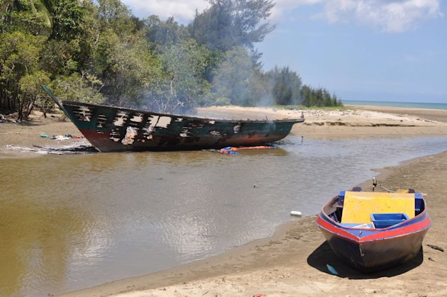 A burnt sampan (L), a small boat, sits on the beach in Kampung Tanduo, where troops stormed the camp of an armed Filipino group, in Lahad Datu, Sabah state, March 9, 2013, in this handout picture provided by Malaysia's Ministry of Defence. Security officials said many militants escaped the military attacks aimed at a coastal village where they had been holed up for weeks. The obscure group is believed to be at large in surrounding oil palm estates. Picture taken March 9, 2013. REUTERS/Malaysia's Ministry of Defence/Handout (MALAYSIA - Tags: POLITICS CIVIL UNREST MILITARY) ATTENTION EDITORS - THIS IMAGE WAS PROVIDED BY A THIRD PARTY. FOR EDITORIAL USE ONLY. NOT FOR SALE FOR MARKETING OR ADVERTISING CAMPAIGNS. THIS PICTURE IS DISTRIBUTED EXACTLY AS RECEIVED BY REUTERS, AS A SERVICE TO CLIENTS