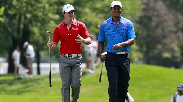 Rory McIlroy (L) of Northern Ireland talks with Tiger Woods of the U.S. as they approach the first green during round one of the BMW Championship golf tournament in Carmel, Indiana (Reuters)
