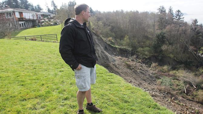 Terry Swanson, University of Washington geologist and resident of Whidbey Island, Wash., stands on a residential lawn next to the edge of Wednesday's massive landslide near Coupeville, Wash., Thursday, March 28, 2013. Authorities spent the day assessing the damage and danger to homes remaining near the slide as nervous residents waited for more detailed information about how safe the area is. (AP Photo/Manuel Valdes)