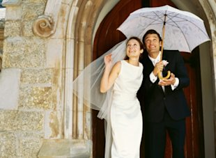 Married couple under umbrella at wedding
