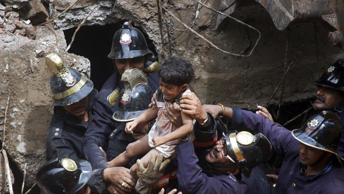 Rescue workers carry a girl who was rescued from the rubble at the site of a collapsed residential building in Mumbai