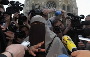 Wearing a niqab, Kenza Drider, the first woman arrested under France's new ban, addresses the media in front of Notre Dame Cathedral on April 11, 2011. (Photo: Pascal Le Segretain/Getty Images) 