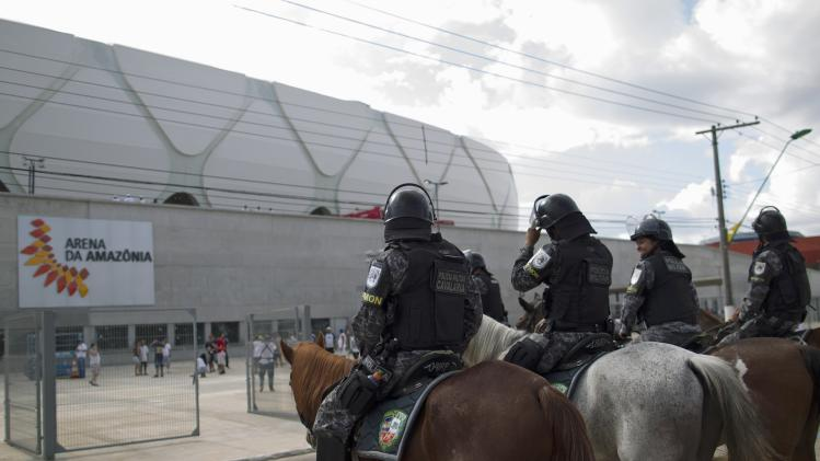 Riot police watch over the Arena Amazonia Vivaldo Lima soccer stadium in Manaus