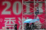 <p>A worker prepares a promotional 2013 banner outside a shopping mall in Hong Kong on Saturday. As the clock strikes 12 on Monday, millions will pop champagne corks and light fireworks while others indulge in quirkier New Year's rituals like melting lead, leaping off chairs or gobbling grapes.</p>