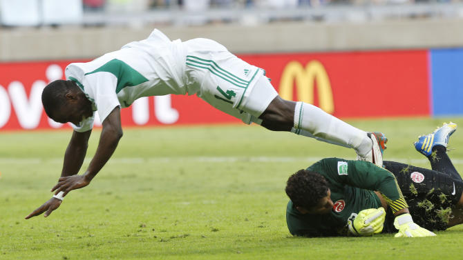 Nigeria's Anthony Ujah, left, is stopped by Tahiti goalkeeper Mikael Roche during the soccer Confederations Cup group B match between Tahiti and Nigeria in Belo Horizonte, Brazil, Monday, June 17, 2013. (AP Photo/Bruno Magalhaes)
