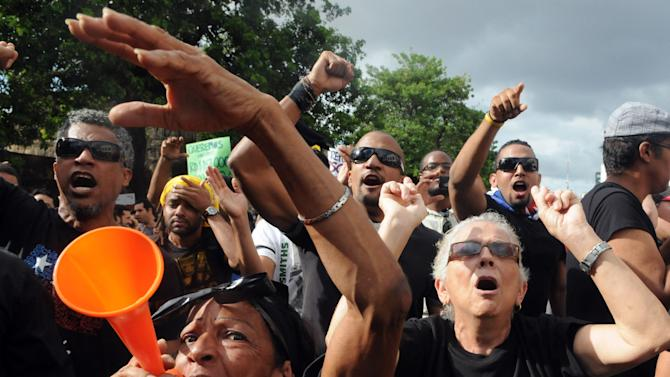 Dominicans shout slogans during a demonstration against the fiscal reform in Santo Domingo, Dominican Republic, Sunday, Nov. 11, 2012. Hundreds of Dominicans protested against the government of Danilo Medina who presented to Congress the disputed tax legislation as a way to help close the $4.6 billion deficit in the government's budget. The measure will increase the general sales tax to 18 percent from 16 percent, will raise the price of gasoline and impose taxes on basic food products. (AP Photo/Manuel Diaz)
