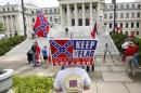 People participate in a rally sponsored by the Magnolia State Heritage Campaign outside the state Capitol, Monday, July 6, 2015, in Jackson, Miss. Jeppie Barbour, a brother of former Mississippi Gov. Haley Barbour, is pushing state leaders to keep the Confederate battle emblem on the state flag. (AP Photo/Rogelio V. Solis)