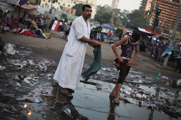 An Egyptian protester washes his clothes in water from a broken pipe in Tahrir Square during continuing protests as the country awaits the outcome of a presidential runoff vote in Cairo, Egypt, Saturd