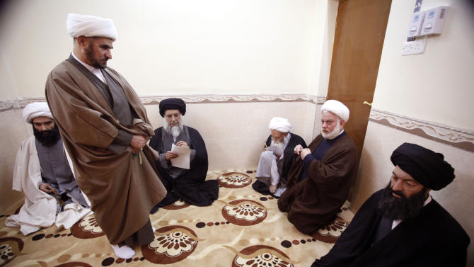 In this picture taken on Feb. 18, 2012, a man, left, and second from right, are seen with wax figures depicting Shiite clerics at the wax museum in the Shiite holy city of Najaf, 100 miles (160 kilometers) south of Baghdad, Iraq.   Even before they go on display, the wax figures have become embroiled in controversy. (AP Photo/Alaa al-Marjani)