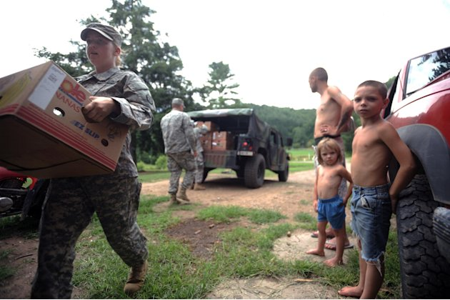 Spc. Megan Pena, left, with the W.Va. National Guard, carries a box of food to a home in Heaters, W.Va., as Austin Hefner, 7, right, Brianna Dunbar, 4, center, and Billy Dunbar Jr., 25,  watch Thursda