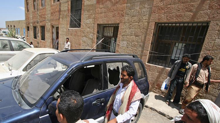 Yemenis gather around a damaged vehicle purported to belong to an American teacher shot by gunmen in Taiz, Yemen, Sunday, March 18, 2012. Two gunmen on a motorcycle shot dead early Sunday an American teacher working at a language institute in a central Yemeni city, the region's provincial governor said. (AP Photo/Anees Mahyoub)