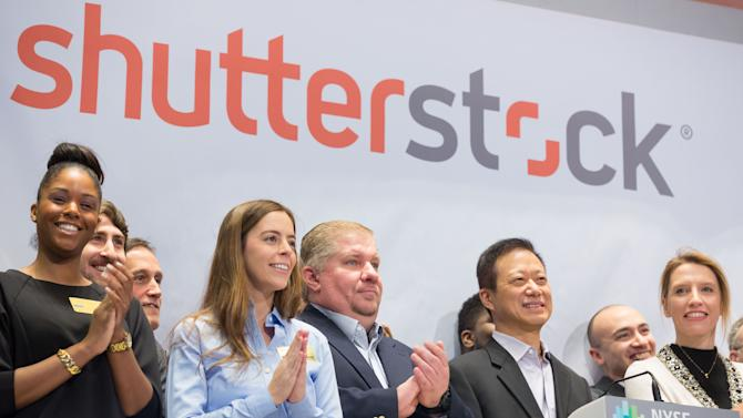 In this image provided by the NYSE, Shutterstock's Chief Technology Officer, James Chou, joined by members of the company's leadership team and Fast Company's Associate Editor, J.J. McCorvey rings the opening bell at The New York Stock Exchange in New York City. (AP Photo/NYSE, Ben Hider)