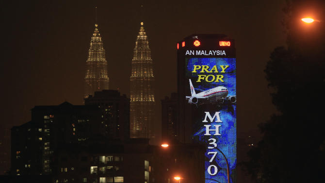"An office building is illuminated with LED lights displaying ""Pray for MH370"" next to Malaysia's landmark Petronas Twin Towers in Kuala Lumpur, Malaysia, Wednesday, March 19, 2014. Countless theories have surfaced about the disappearance of Malaysia Airlines Flight 370 nearly two weeks ago. (AP Photo/Lai Seng Sin)"