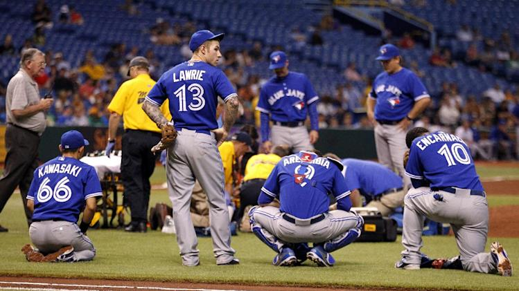 Members of the Toronto Blue Jays, from left, Munenori Kawasaki, Brett Lawrie, J.P. Arencibia, and Edwin Encarnacion look on as starting pitcher J.A. Happ is attended to by medical personnel after being hit in the head by a line drive off the bat of Tampa Bay Rays' Desmond Jennings during the second inning of a baseball game Tuesday, May 7, 2013, in St. Petersburg, Fla. (AP Photo/Mike Carlson)