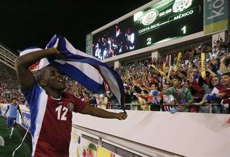 Costa Rica's Campbell holding a national flag celebrates after his team beat Mexico in their 2014 World Cup qualifying match in San Jose