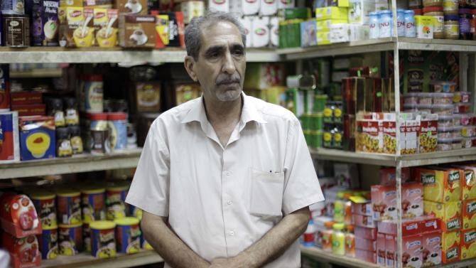 """Abdul Hadi al-Obeidi, 65, a Sunni Muslim and is married to a Shiite woman who manages a grocery store in the Karrada Neighborhood of Baghdad, Iraq, poses for a portrait  Wednesday, July 4, 2012. """"Every time I leave my house, I don't know what will happen to me. I can only leave it in God's hands,"""" he said. (AP Photo/Khalid Mohammed)"""