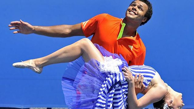 Jo-Wilfried Tsonga of France performs with 'can-can' dancer Pieta Farrell during a photo opportunity following a training session during the Australian Open tennis tournament in Melbourne January 22, 2012 (Reuters)