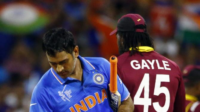 India's captain MS Dhoni lights up the bails as he flips them off the stumps after India defeated the West Indies by four wickets at the Cricket World Cup in Perth