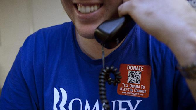 Bryan Munks, 19, of Arlington, Va., makes calls for the Romney campaign while wearing a quick response code sticker, or QR, in Fairfax, Va., on Tuesday, June 19, 2012.   The presidential ground game has gone high tech, marrying old-school organizing work with innovative digital tools.   The T-shirts that Romney campaign volunteers wear in Virginia feature a digital code that voters can zap with their smart phones to learn more about the Republican presidential hopeful, which gives Romney field organizers valuable information on how to reach them in the future.(AP Photo/Jacquelyn Martin)