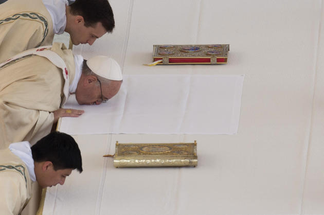 Pope Francis, middle, kisses the altar as he arrives to celebrate his first canonization ceremony in St. Peter's Square at the Vatican, Sunday, May 12, 2013. The pontiff will canonize Antonio Primaldo