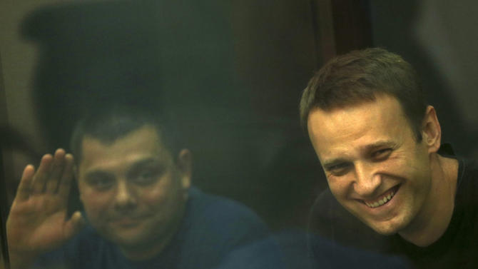 Russian opposition leader Alexei Navalny, right, and his former colleague Pyotr Ofitserov, left, are seen through a cage window in a courtroom in Kirov, Russia on Friday, July 19, 2013. A Russian court is deliberating on a surprise request by prosecutors to free opposition leader Alexei Navalny one day after he was convicted of embezzlement and sentenced to five years in prison. (AP Photo/Evgeny Feldman)