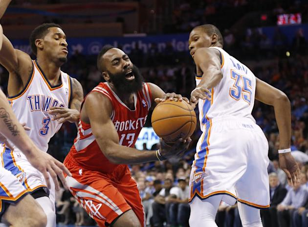 Houston Rockets guard James Harden (13) drives between Oklahoma City Thunder forward Perry Jones (3) and forward Kevin Durant (35) during the first quarter of an NBA basketball game in Oklahoma City,