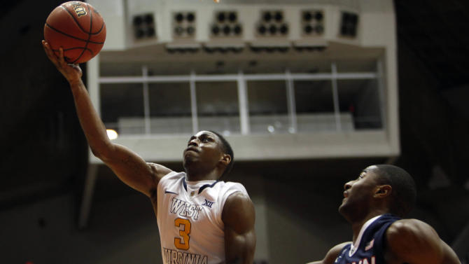 West Virginia guard, Juwan Staten, left, goes to the basket against UConn guard Rodney Purvis during a NCAA college basketball game in San Juan, Puerto Rico, Sunday, Nov. 23, 2014. (AP Photo/Ricardo Arduengo)