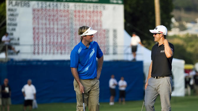 Russell Henley, left, and Scott Langley share a moment before putting on the 18th green during the third round of the Sony Open golf tournament, Saturday, Jan. 12, 2013, in Honolulu. Henley and Langley are tied for first place at 17 under going into the final round Sunday.  (AP Photo/Marco Garcia)