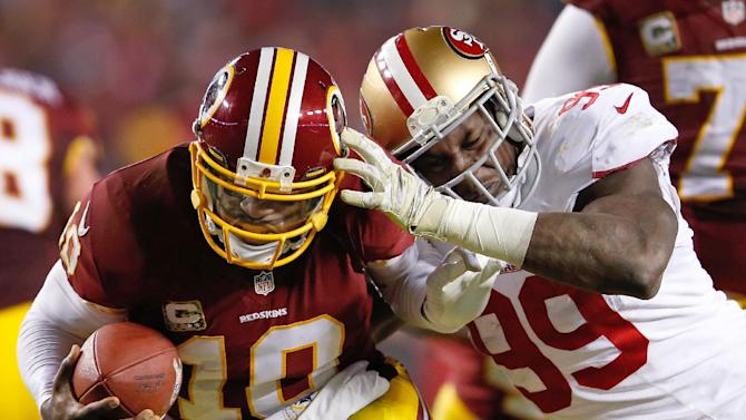FILE - In this Nov. 25, 2013, file photo, Washington Redskins quarterback Robert Griffin III is sacked by San Francisco 49ers outside linebacker Aldon Smith during an NFL football game in Landover, Md. Smith appreciates these playoffs a little more. After a five-game absence from the 49ers to undergo treatment for substance abuse earlier this season, Smith is encouraged by the big strides he has made to better himself off the football field. (AP Photo/Evan Vucci, File)