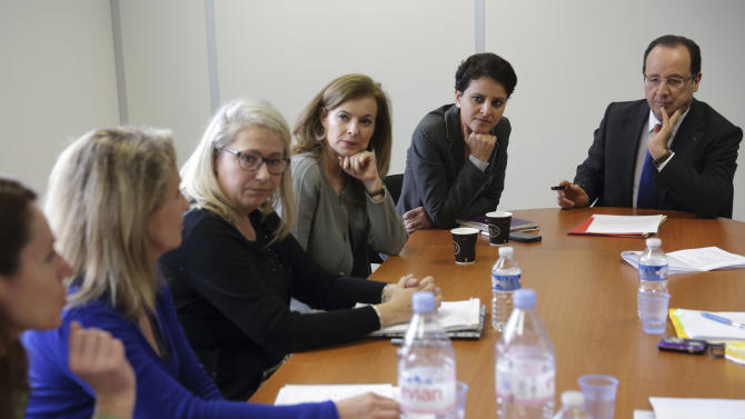"""French President Francois Hollande, right, his companion Valerie Trierweiler, third right, and Minister of Women's Rights Najat Vallaud-Belkacem, second right, attend a meeting with women at """"Force Femmes"""", an association which helps unemployed women over 45-years old in Paris, Friday March 8, 2013. Hollande is proposing legislation to get more dads on long-term paternity leave and moms back to work faster. Hollande, a never-married father of four, also wants more state aid for single parents whose partners fail to pay child support. (AP Photo/Philippe Wojazer/Pool)"""