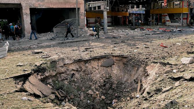 In this photo released by the Syrian official news agency SANA, Syrians walk past a crater caused by an explosion at the scene where triple bombs exploded at the Saadallah al-Jabri square, in Aleppo city, Syria, Wednesday Oct. 3, 2012. Three powerful explosions rocked the main square in a government-controlled central district of Aleppo on Wednesday, the Syrian state-run TV said. Activists reported multiple casualties and heavy material damage. (AP Photo/SANA)