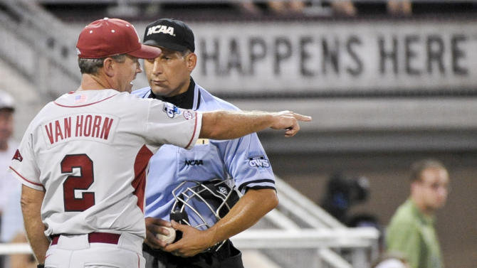 Arkansas coach Dave Van Horn (2) argues with home plate umpire Perry Costello over an interference call against Bo Bigham in the fourth inning of an NCAA College World Series baseball game against South Carolina, in Omaha, Neb., Monday, June 18, 2012. (AP Photo/Ted Kirk)