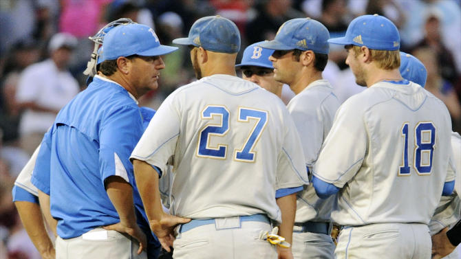 UCLA coach John Savage, left, speaks to pitcher Adam Plutko, center right, on the mound in the fourth inning of Game 1 in their NCAA College World Series baseball finals against Mississippi State, Monday, June 24, 2013, in Omaha, Neb. (AP Photo/Francis Gardler)