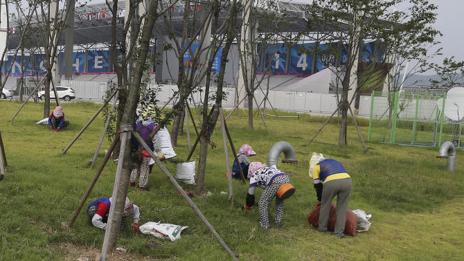 Workers clip grass and dig up weed in a grass area outside the 17th Asian Games main stadium ahead of the opening ceremony in Incheon, west of Seoul, South Korea, Monday, Sept. 15, 2014. The games will be held in the South Korea's western city from Sept. 19 to Oct. 4. (AP Photo/Rob Griffith)