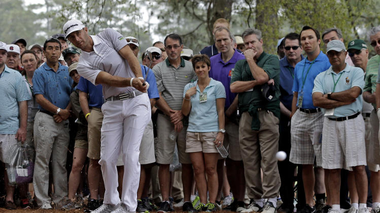Dustin Johnson takes his second shot on off the rough on the first hole during the second round of the Masters golf tournament Friday, April 12, 2013, in Augusta, Ga. (AP Photo/Darron Cummings)