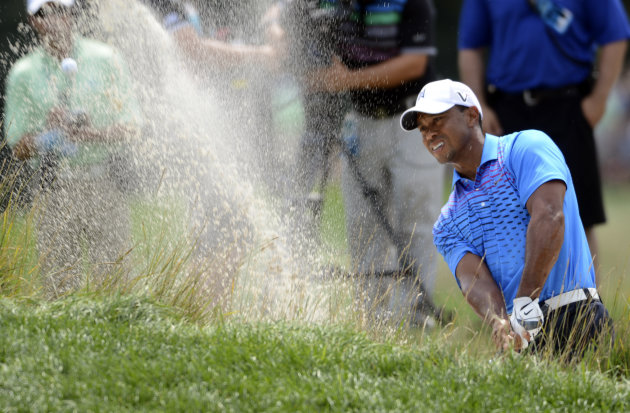 Tiger Woods blasts out of a sand trap on the second hole during the second round of The Barclays golf tournament at Bethpage State Park in Farmingdale, N.Y., Friday, Aug. 24, 2012. (AP Photos/Henny Ra