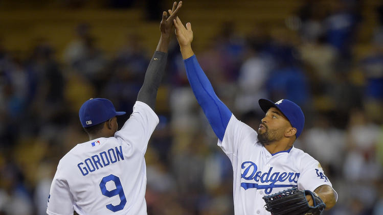 Los Angeles Dodgers' Dee Gordon, left, and Matt Kemp celebrate after the Dodgers defeated the San Diego Padres 2-1 in a baseball game, Thursday, Aug. 21, 2014, in Los Angeles. (AP Photo/Mark J. Terrill)