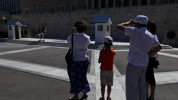 Tourists watch two presidential guards perform outside the Greek parliament in central Athens, on Saturday, June 16, 2012.  Greeks cast their ballots this Sunday for the second time in six weeks, after May 6 elections left no party with enough seats in Parliament to form a government and coalition talks collapsed.(AP Photo/Petros Giannakouris)
