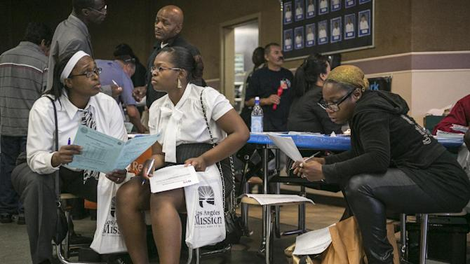 Job seekers Antoinette Zinnerman, 39, left, with her daughter, Kennesha, 19, middle, inquire for positions at the 12th annual Mission career fair on Thursday, June 6, 2013 in the skid raw area of Los Angeles. At right, Akili Sanders, 38. The Labor Departmetn said Thursday, July 25, 2013 that ehe number of Americans applying for unemployment benefits rose by 7,000 last week to a seasonally adjusted 343,000. The increase follows a drop of 22,000 the previous week. But the broader trend is consistent with an improving job market. (AP Photo/Damian Dovarganes)