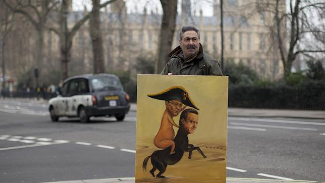 Political artist Kaya Mar poses for photographs with his horsemeat scandal painting which depicts French President, Francois Hollande, and British Prime Minister, David Cameron, in London, Wednesday, Feb. 13, 2013.  British authorities on Tuesday raided a slaughterhouse and a meat processing company suspected of selling horsemeat labeled as beef for kebabs and burgers, shutting them down temporarily and seizing all the meat found.  Millions of burgers and frozen meals have been recalled around Europe and many accusations have been made, but so far it's not clear how horsemeat got introduced into so many beef products. French authorities have already pointed to an elaborate supply chain that involved Romanian butchers and Dutch and Cypriot traders that resulted in horsemeat disguised as beef being sold in meals like lasagne and moussaka to consumers around the continent.  (AP Photo/Matt Dunham)