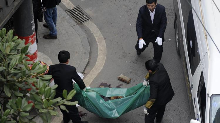 People move a body away from a crime scene after a knifing incident in Changsha, Hunan province