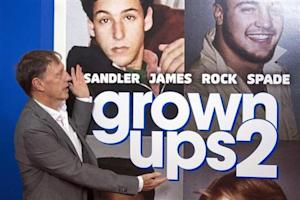 """Director Dennis Dugan gestures to the poster in the backdrop as he arrives for the premiere of the film """"Grown Ups 2"""" in New York"""