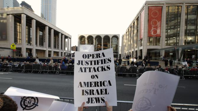 Protesters holds signs during a demonstration across from Lincoln Center and the New York Metropolitan Opera in New York