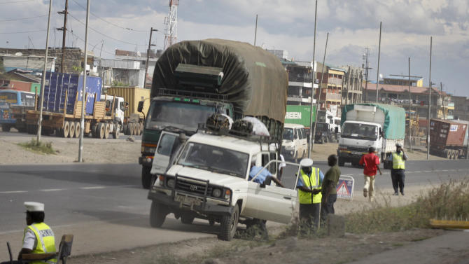 In this photo taken Thursday, Dec. 6, 2012, Kenyan police stop a car at a vehicle checkpoint in Nairobi, Kenya. The drivers of minibuses say Kenya's new traffic laws, which carry higher fines and bigger jail sentences, will result primarily in one thing: higher bribes. (AP Photo/Khalil Senosi)