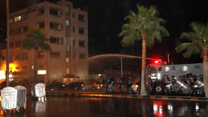 A Jordanian military water cannon vehicle sprays water to disperse protesters near the Interior Ministry Circle during a demonstration following an announcement that Jordan would raise fuel prices, including a hike on cooking gas in Amman,  Jordan, Wednesday, Nov. 14, 2012. (AP Photo/Mohammad Hannon)