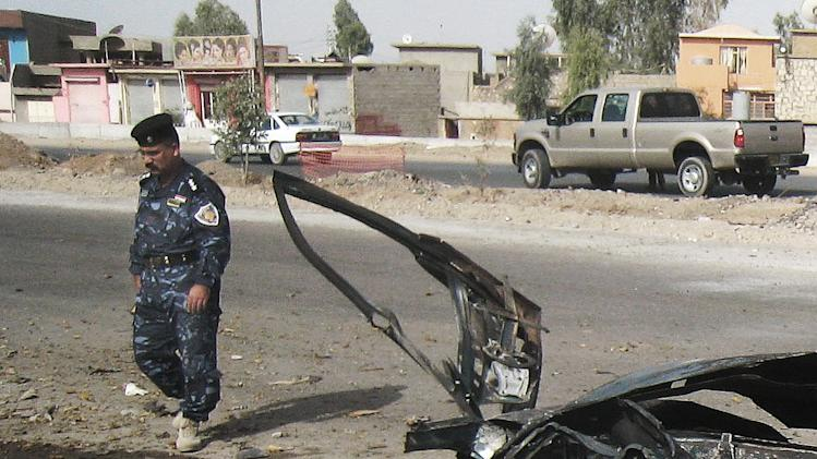 An Iraqi police man inspects the scene of a car bomb attack in Kirkuk, 290 kilometers (180 miles) north of Baghdad, Iraq, Thursday, Aug 16, 2012. Five separate bombings in central and northern Iraq, killed and wounded scores of people early Thursday, police said. (AP Photo/Emad Matti)