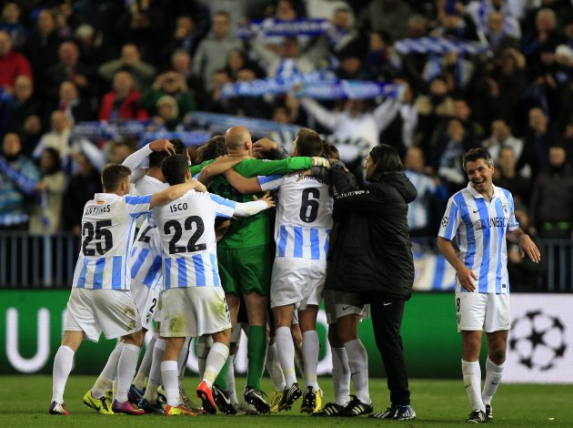 Malaga's players celebrate after defeating Porto during their soccer match at La Rosaleda stadium in Malaga
