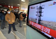 Travellers watch a TV screen broadcasting news about North Korea's rocket launch, at a railway station in Seoul on December 12, 2012. North Korea launched a long-range rocket which Japanese authorities said passed over its southern island chain of Okinawa