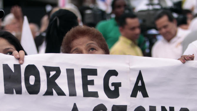 A woman holds a sign that reads in Spanish 'Noriega Murderer' during a demonstration against the return of the Panama's former strongman Manuel Noriega in Panama City, Friday, Dec. 9, 2011. Noriega, who will be extradited from France to Panama on Sunday, was ousted in the United States' 1989 invasion of Panama, convicted of drug racketeering in Miami and served 20 years in a U.S. prison. The U.S. extradited Noriega to France in 2010 to face charges he laundered some $3 million in drug money, where he was convicted and handed a seven-year sentence. Noriega, now 77, will be jailed again in Panama, for the slayings of two political opponents in the 1980s. (AP Photo/Arnulfo Franco)
