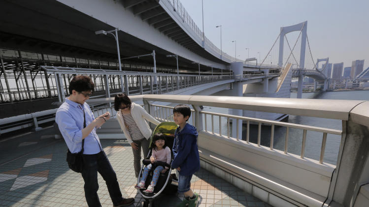 In this May 5, 2013 photo, a father takes a photo of his family on the walkway of the Rainbow Bridge in Tokyo. The walk is just over one mile (1.7 kilometers) including the 918-meter-long (just over half a mile) single-span suspension bridge and takes less than an hour one way. A walk on the north side of the bridge provides the panoramic view of Tokyo's skyline. (AP Photo/Itsuo Inouye)